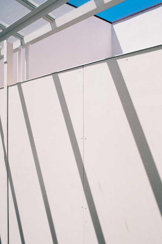 Pormenor do corredor coberto de acesso a apartamentos de dos tapa vistas dos seus pátios privativos, Porto.