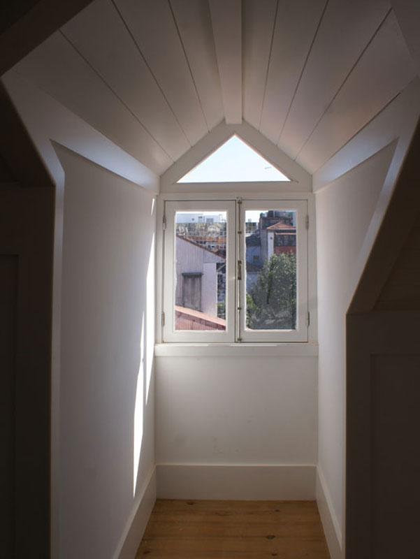 Sala de estar em vão do telhado em edifício reabilitado, rua do Rosário, Porto.